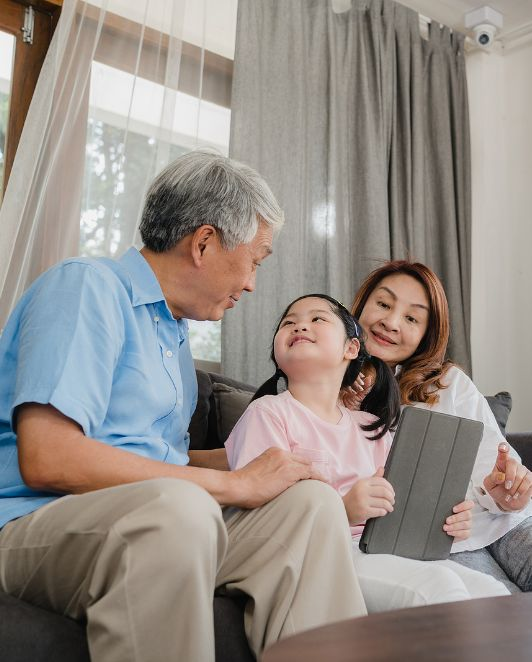 Grandparent reading book with Asian girl